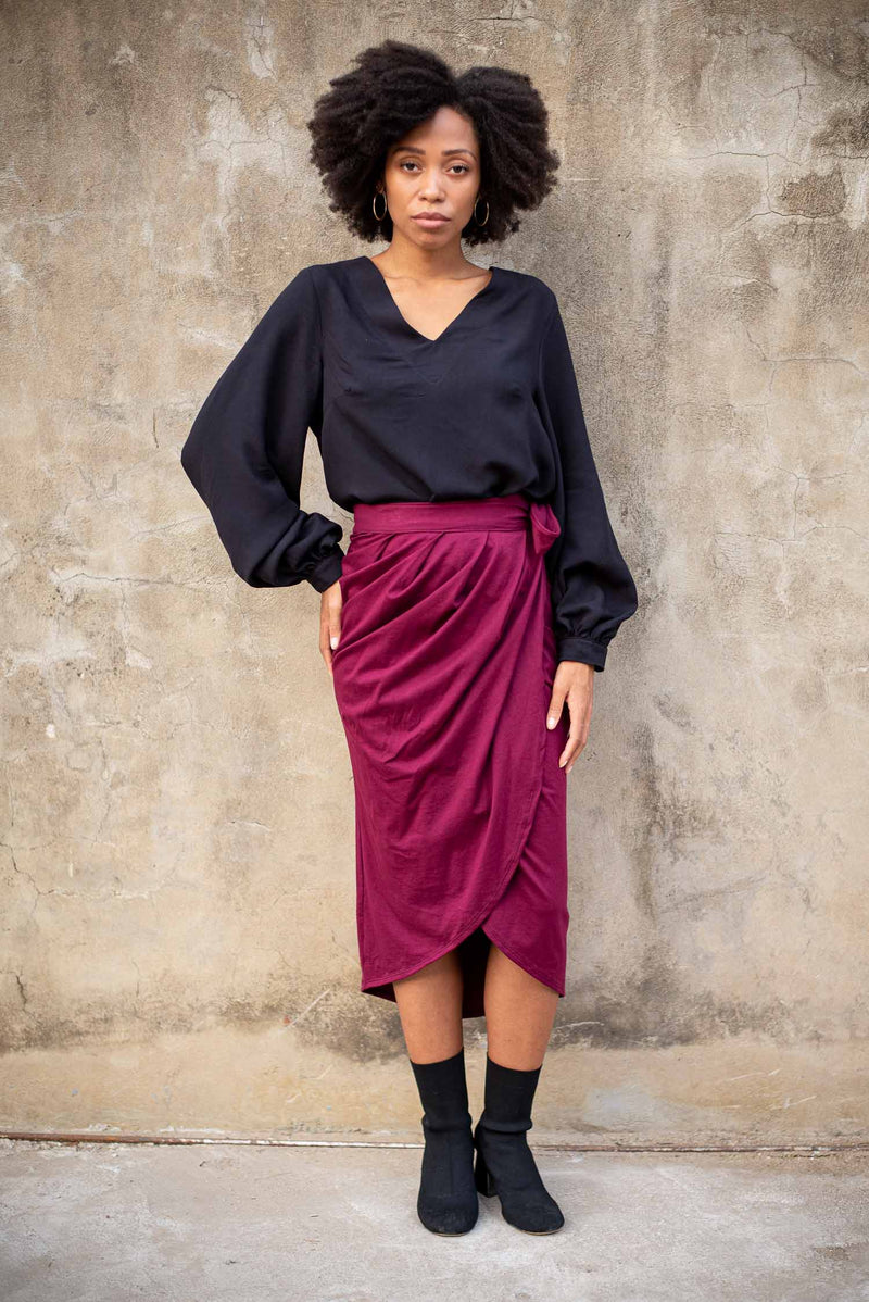 Our sustainable fashion Maly top is seen here in black styled with a chic skirt.