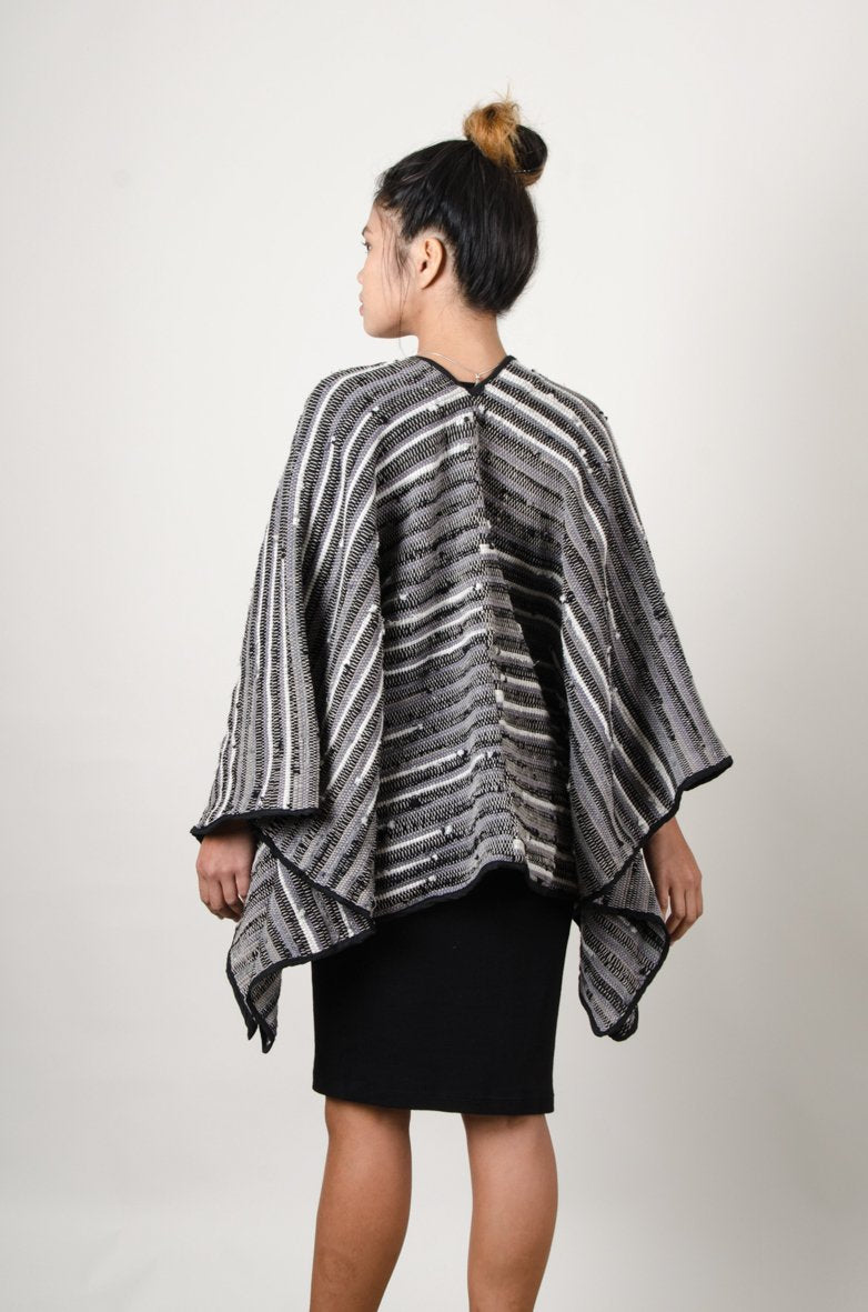 A back image of our fair fashion Manina cape cardigan that shows the drape of the garment.