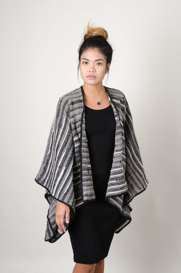 The Manina cape cardigan, seen here in black and grey, is handwoven from scraps of reclaimed materials as part of our zero waste process.