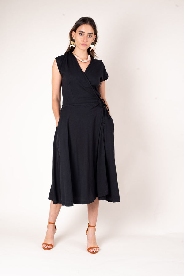 A front view of our sustainable fashion dress with a classic wrap waist and elegant v-neck. Shown here in soft black jersey.