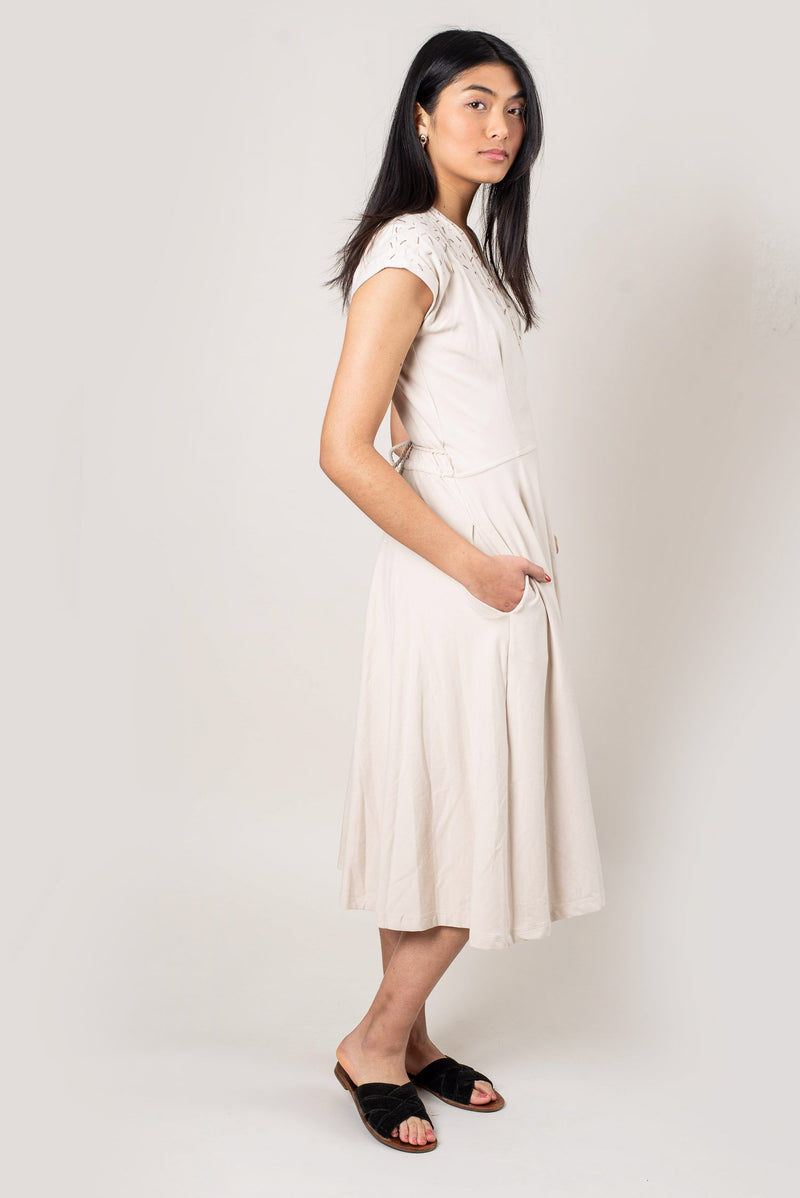 A side image of our ethically made Mekong wrap dress in cream that shows the pockets.