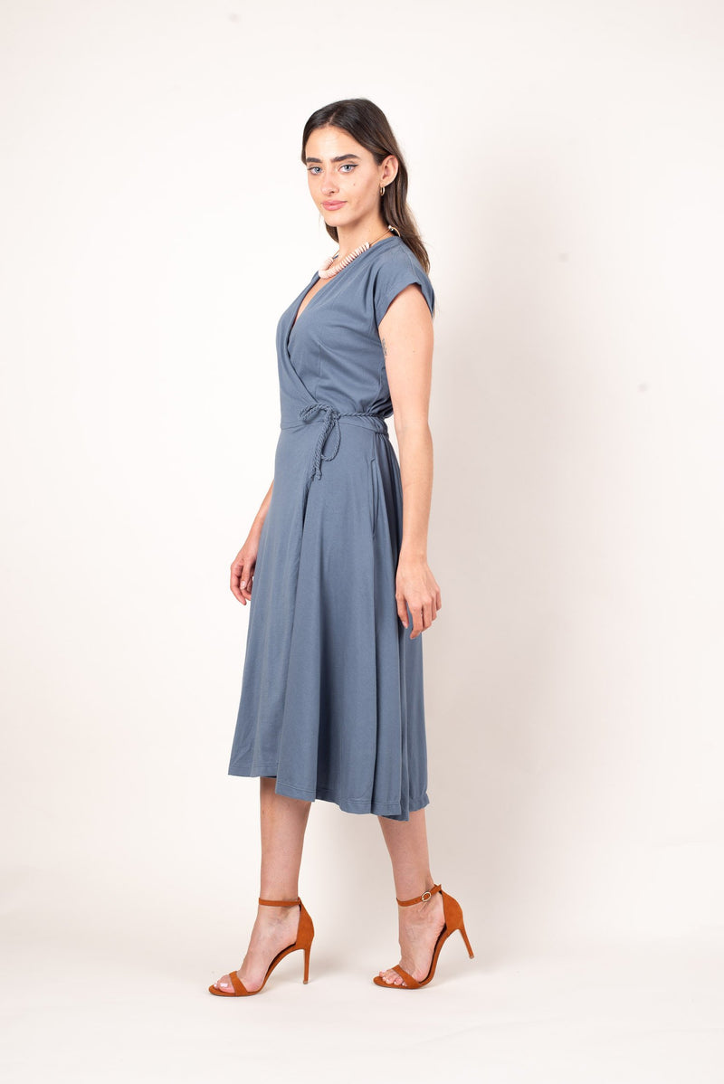 A side view of the draping and flowy dusty blue mekong wrap dress, perfect for warm spring days and summer nights. Perfect for any zero waste capsule wardrobe.
