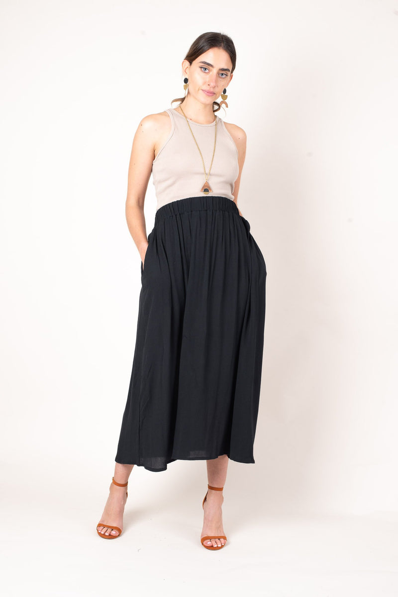 A front view of the mid-calf length midi skirt in black crepe. This skirt features a high waist and keep pockets for comfort and convenience.