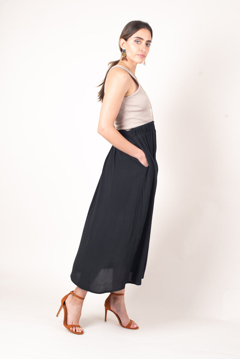 A side view showing off the pockets on our soft and flowing midi skirt which easily pairs with flats or heels and is perfect for any minimalist capsule wardrobe.