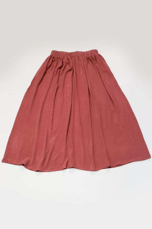 A flat image of our ethically made midi skirt in pink clay crepe.
