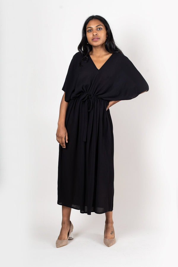 A front view of the loose fitting soft midi dress with a draw string waist in black cotton crepe.