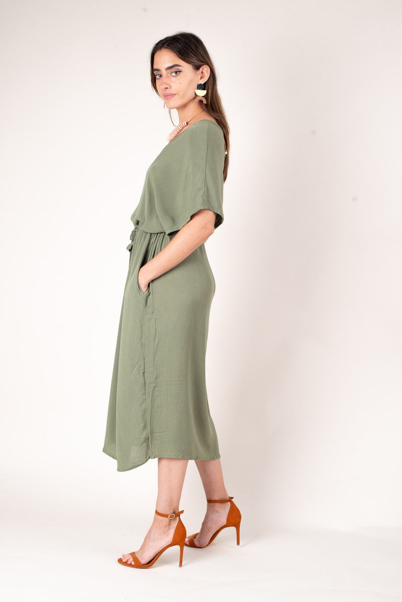 A side view of our green flowing fair fashion dress made from fabric that drapes elegantly.