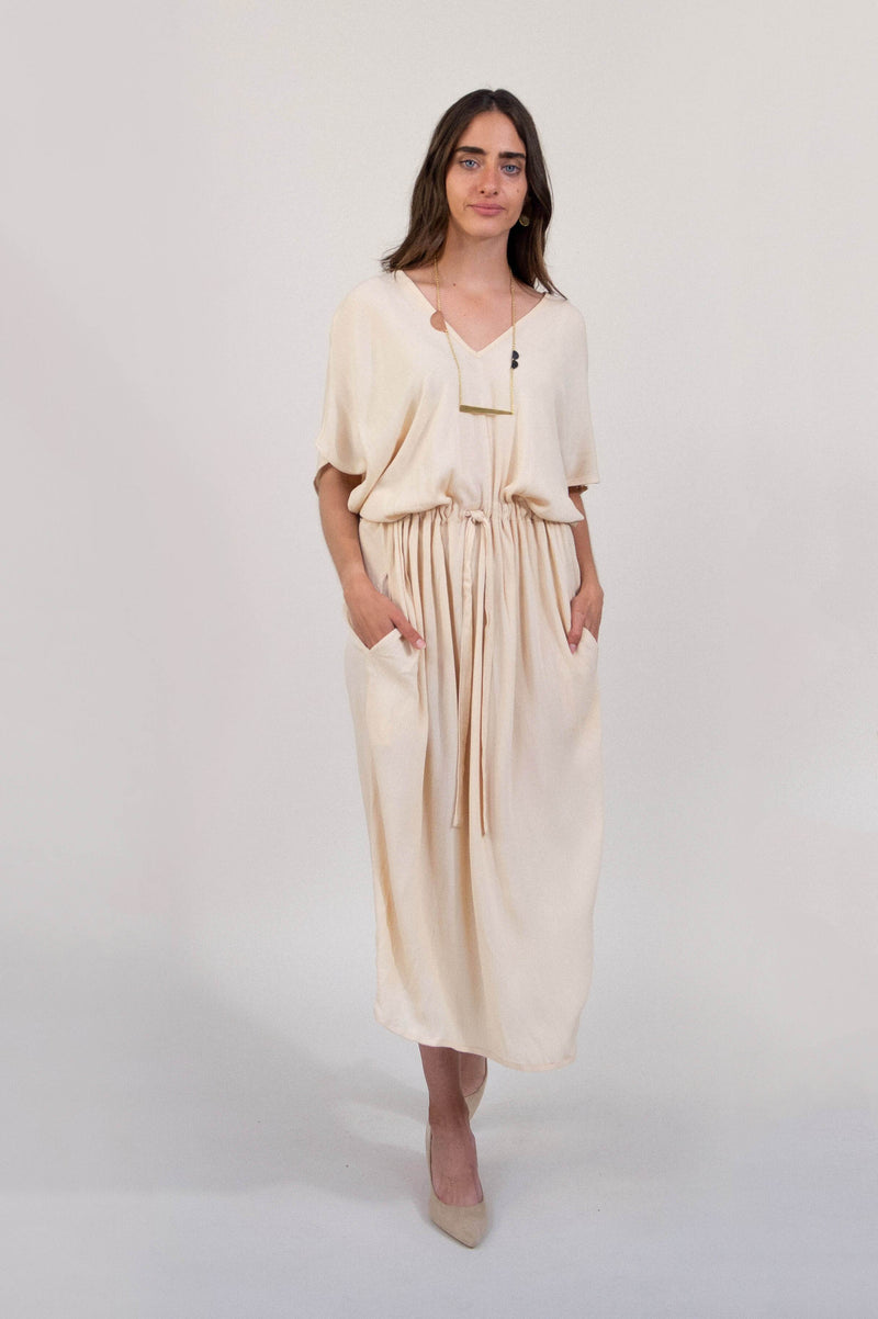 A front view of the kaftan style v-neck midi dress with pockets in a soft off-white palm color.