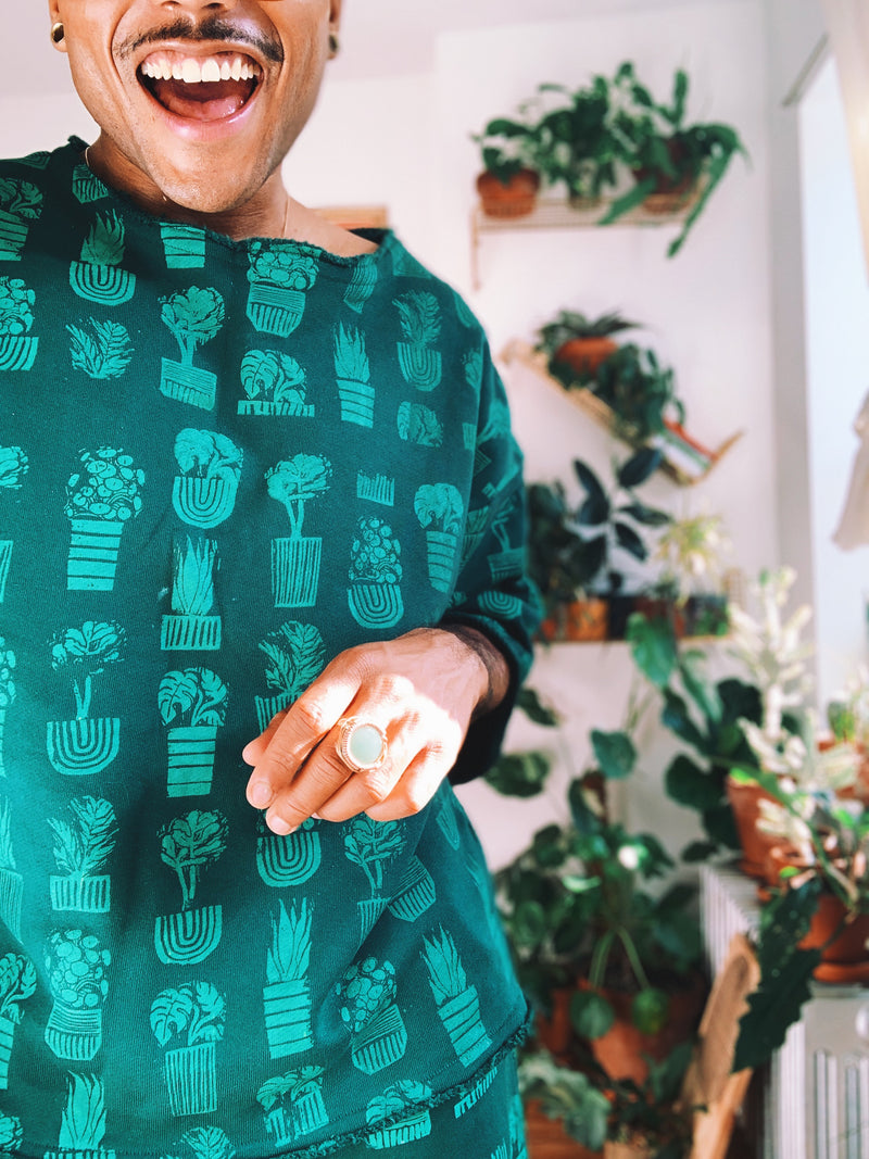 A detail view of the hand-printed potted plant design on our circular fashion sweatshirt, modeled by collaborative designer Plant Kween.