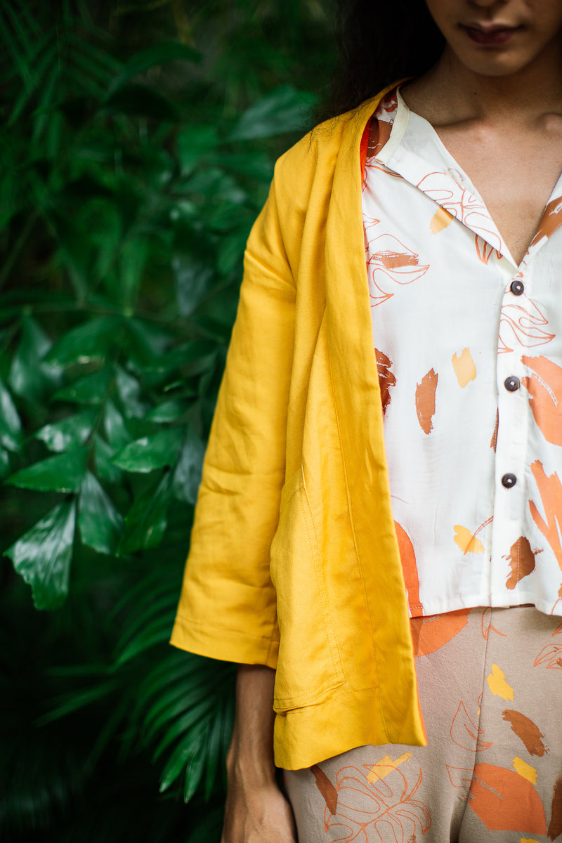 A close up of the hand-carved coconut buttons that close up our gender inclusive Shelby shirt.