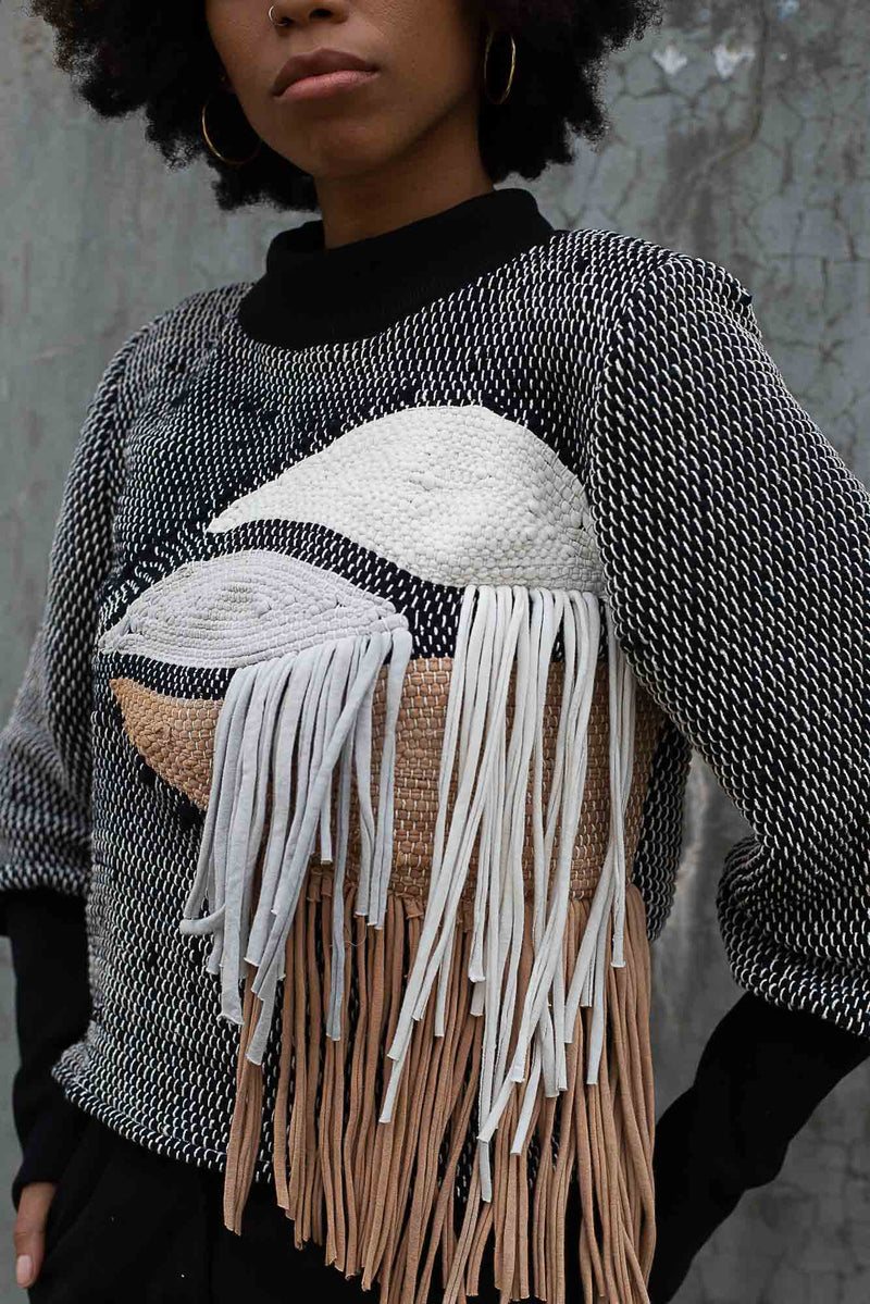 A detail image of the Priya sweater in black and khaki that shows the fringe flowing from the handwoven design.