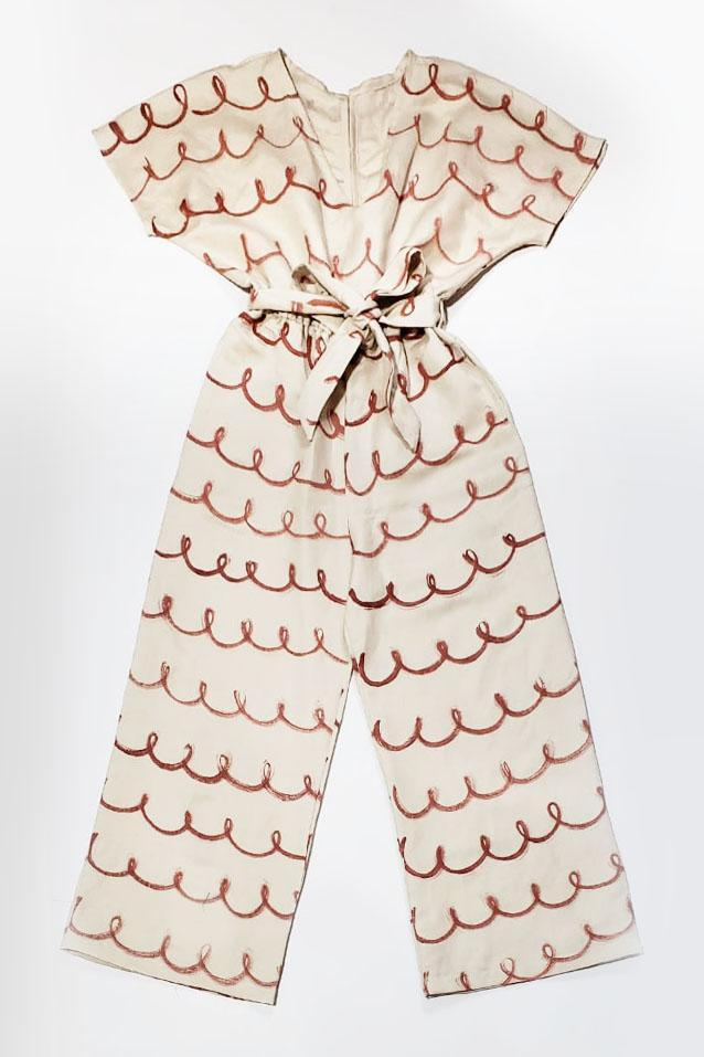 A flat view of the cream linen Rachana jumpsuit with our hand-painted whimsy print.