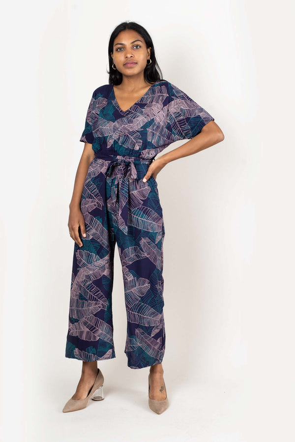 The Rachana jumpsuit, seen here in navy with a banana palm leaf print, is made from reclaimed rayon as part of our unique zero waste process.