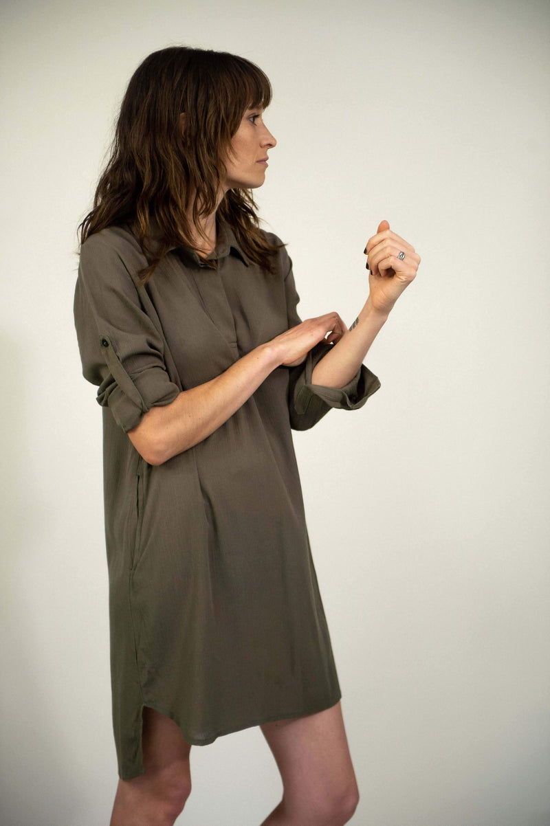 A side view of our ethically made Rachana tunic in olive that shows the button tab closure on the adjustable sleeves.