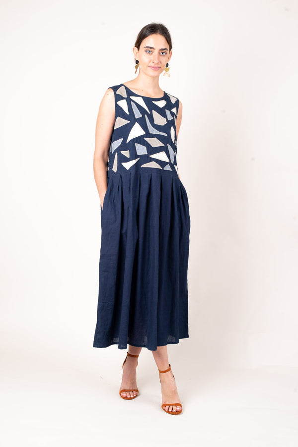 A front full body view of the reclaimed navy linen sea-glass appliqué dress with a pleated skirt and deep pockets.
