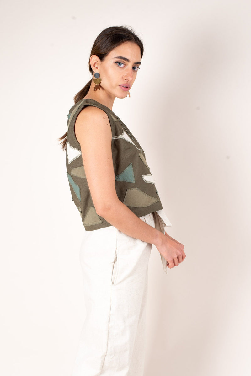 A side view showing off the boxy loose fit of this olive green tank top made from lightweight reclaimed linen.