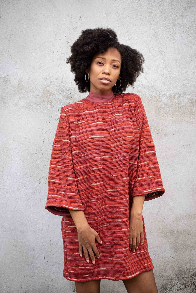 The handwoven Seyha dress, seen here in brick, is made from reclaimed textiles as part of our zero waste process.