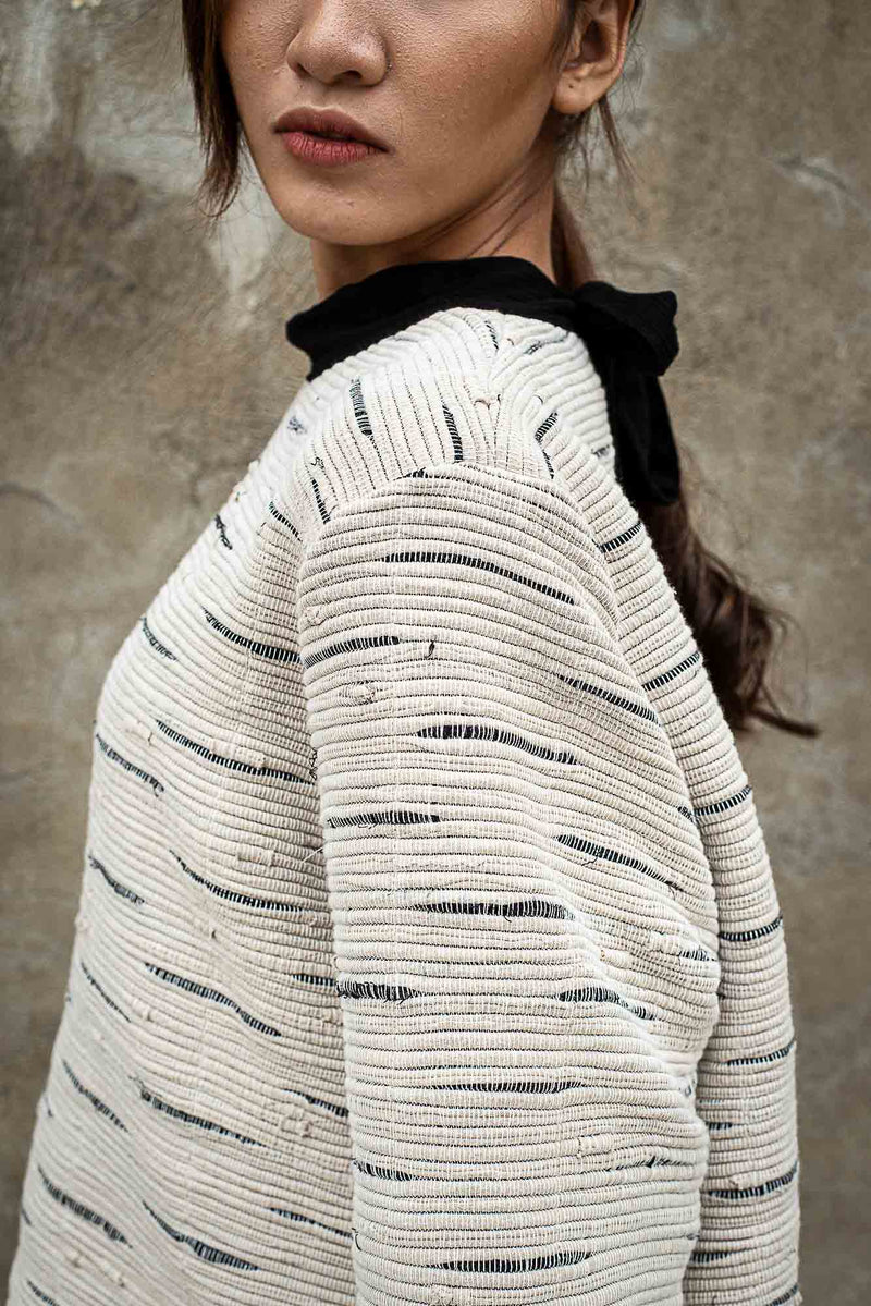 A detail image of our fair fashion Seyha sweater that shows the texture of the handwoven textile.