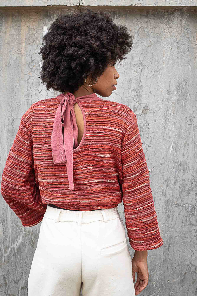 A back view of our Seyha sweater in brick that shows the bow tie closure.