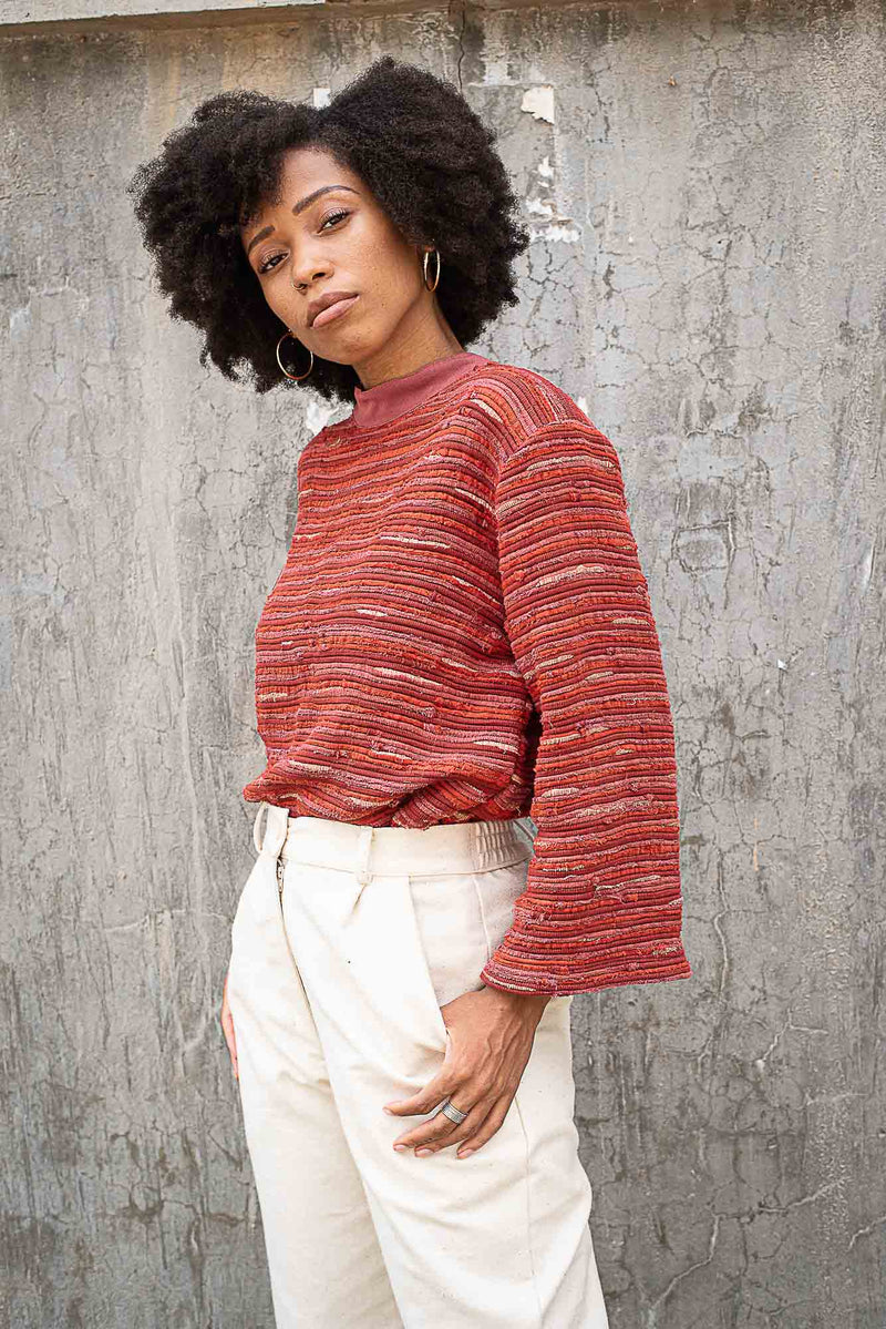 The Seyha sweater can be styled, as seen here, tucked into favorite trousers.