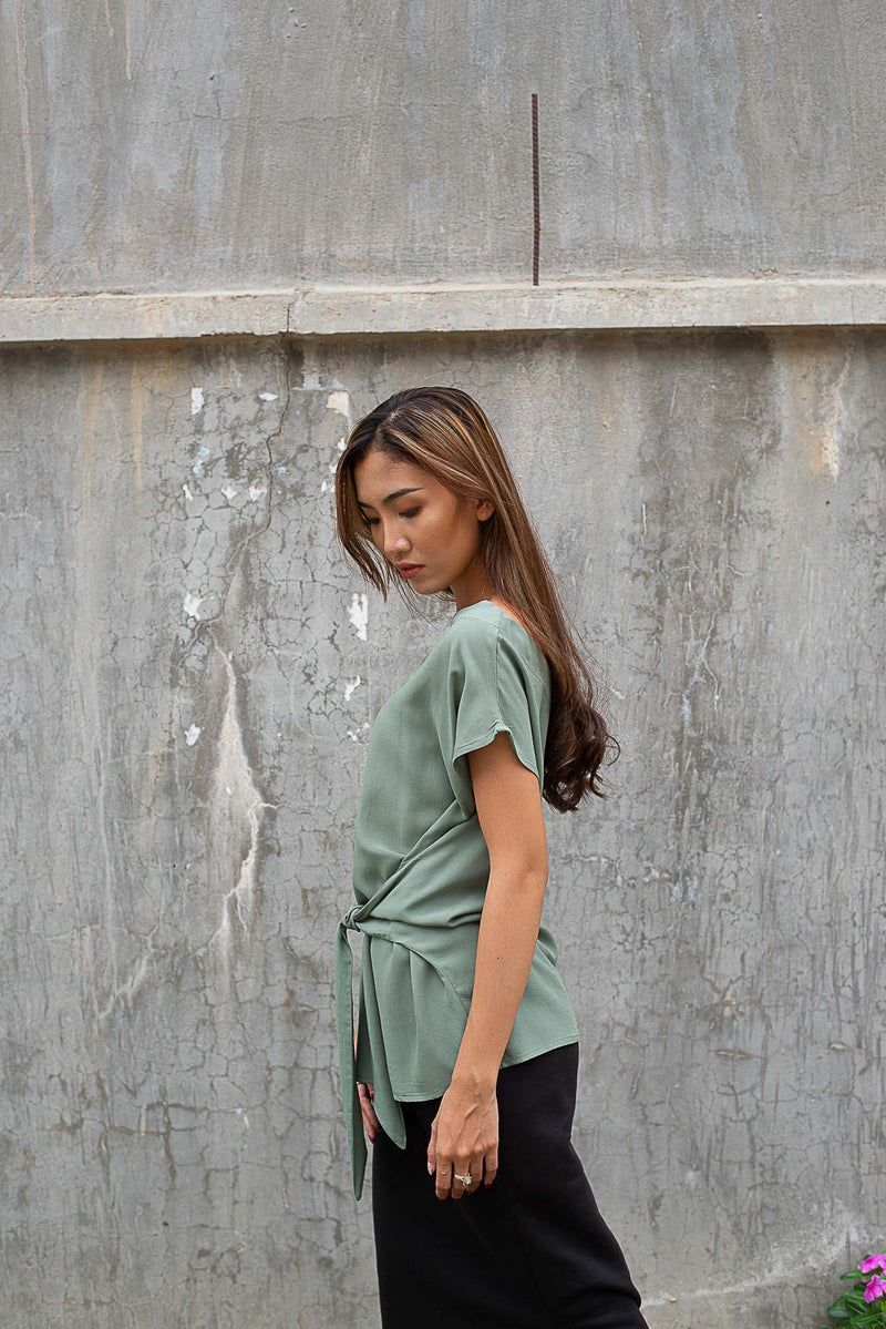 A side view of our circular fashion Sofia top that shows the waist tie detail. Seen here in sage.