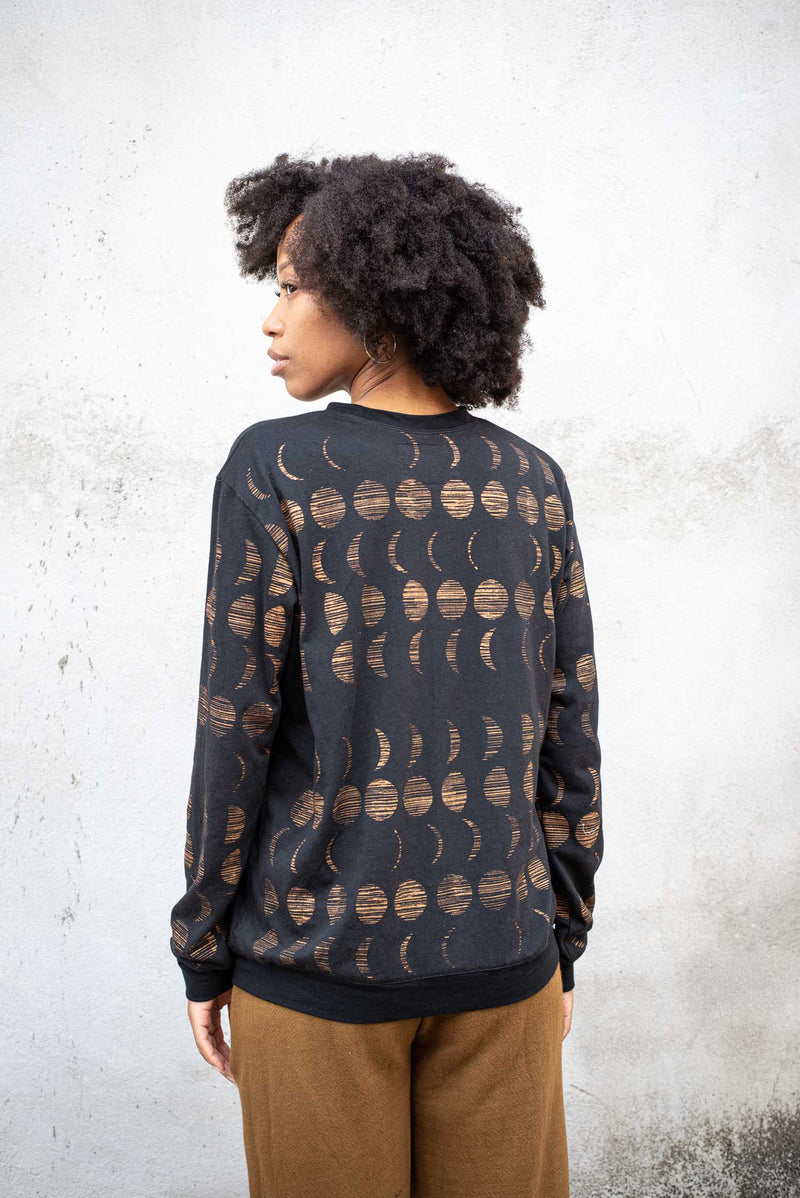 A back view of our circular fashion Sokha top in black with a moon cycle print.