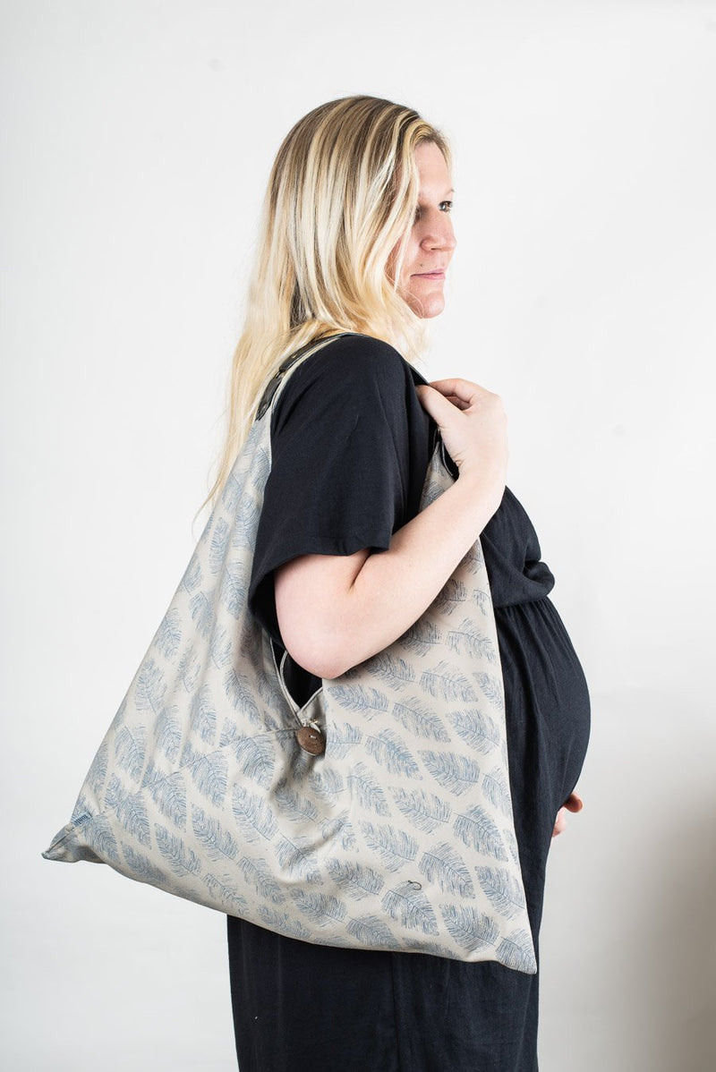 Our ethically made Sol Triangle Tote can be worn over one shoulder, as seen here, or be held in one hand.