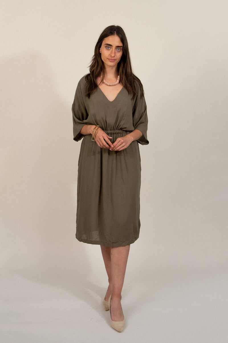 Our ethically made Sothea dress is seen here in olive, styled with low heels and accessories for a chic evening look.