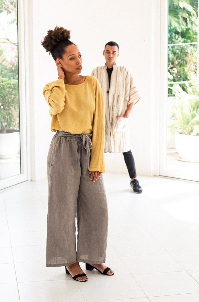 An image of our Sothea pants in grey linen, styled with an elegant top and heels.