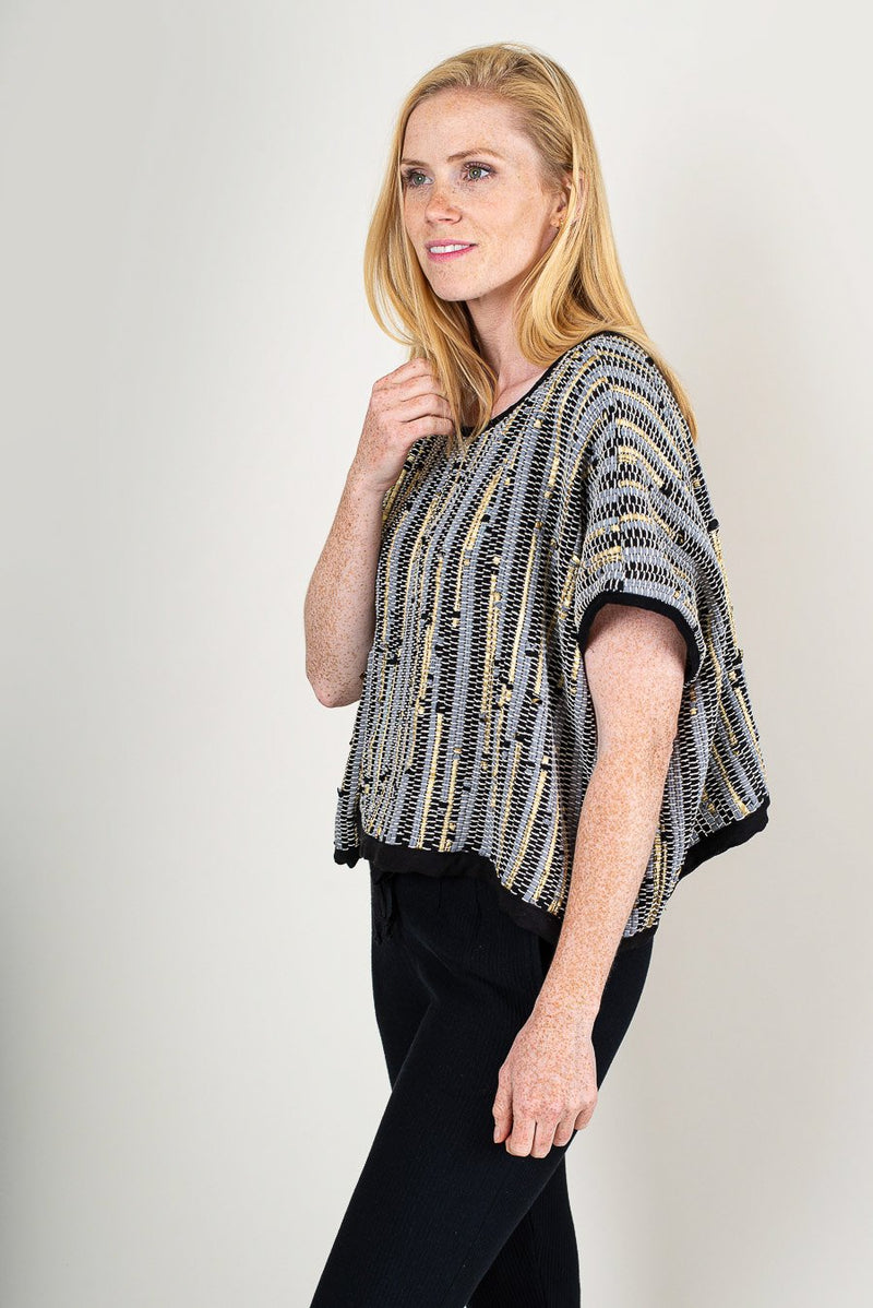 A side view of the handwoven Srey crop top in patina that shows the drape of the garment.