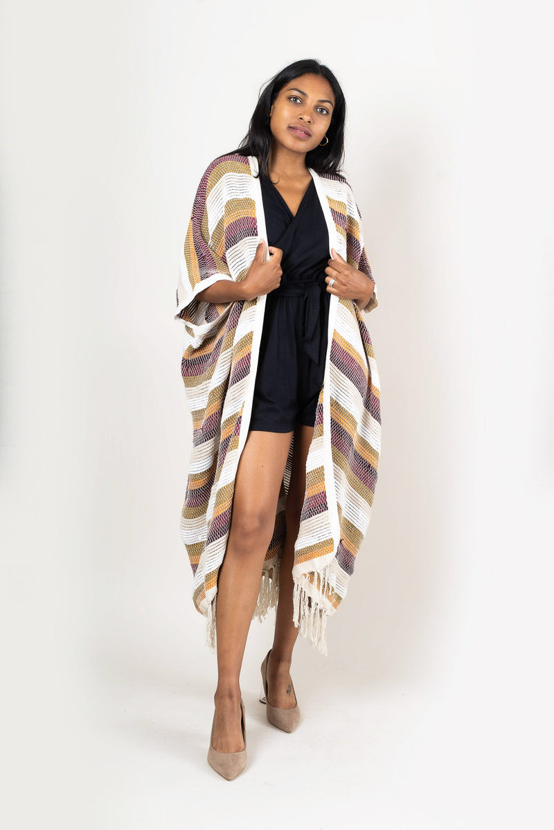 The Srey duster vest, seen here in desert, is an elegant outer layer over evening looks, as styled here.