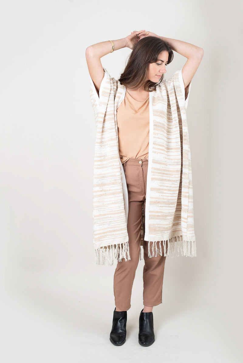 The Srey duster vest, seen here in natural, is finished with a fun fringe. Handwoven as part of our circular fashion process.