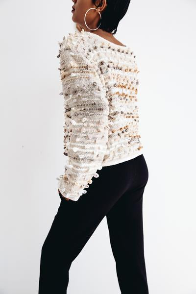 A back view of our sustainably made Srey Oun sweater that shows the allover texture of the yarn bobbles.