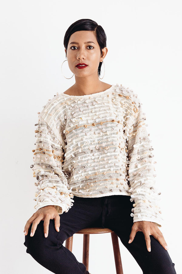 A front view of the ethically made Srey Oun sweater in natural that shows the fun texture of the yarn bobbles.