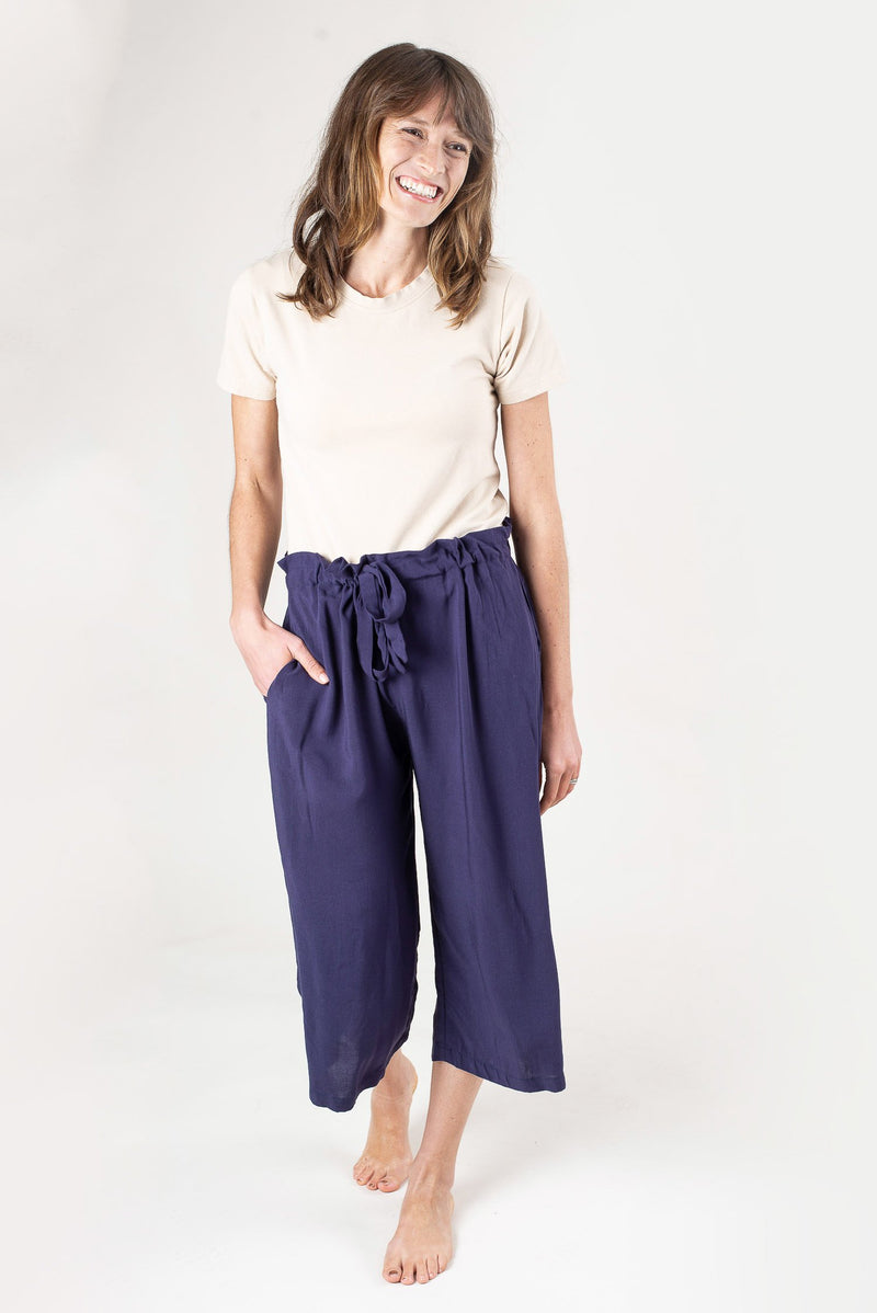 Our Srey Pov culottes, seen here in navy, have a drawstring closure and a paper bag waist.