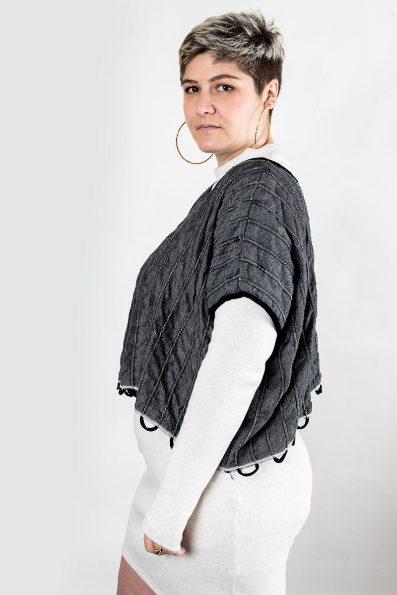 A side view of the Takeo crop top which highlights the yarn loops at the hem.