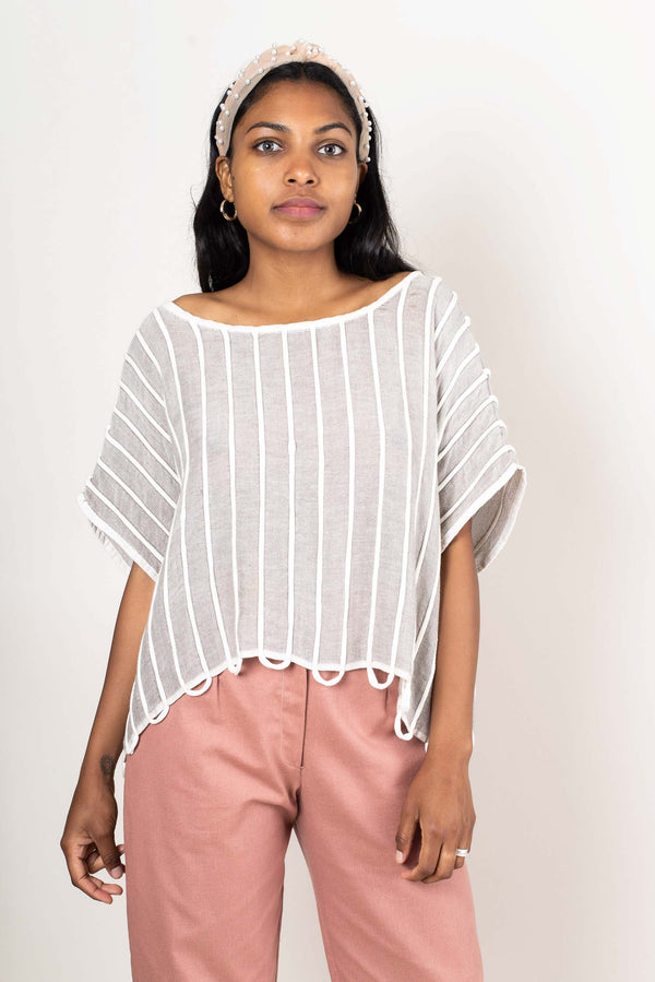 Our Takeo crop top, seen here in grey, is made from reclaimed jersey and cotton yarn as part of our  zero waste process.