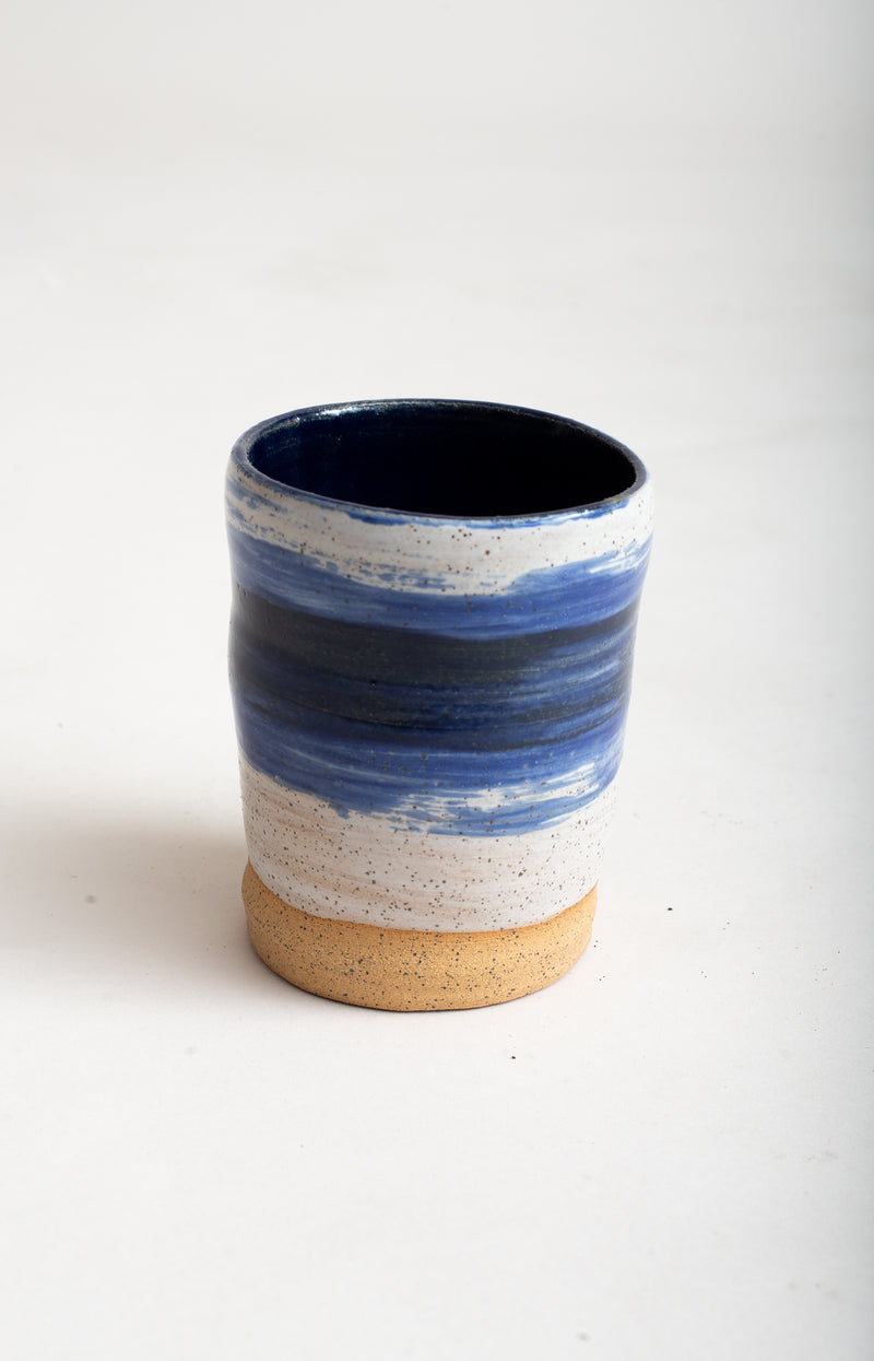 This handmade ceramic mug has a hand-painted blue wave pattern around the center exterior.