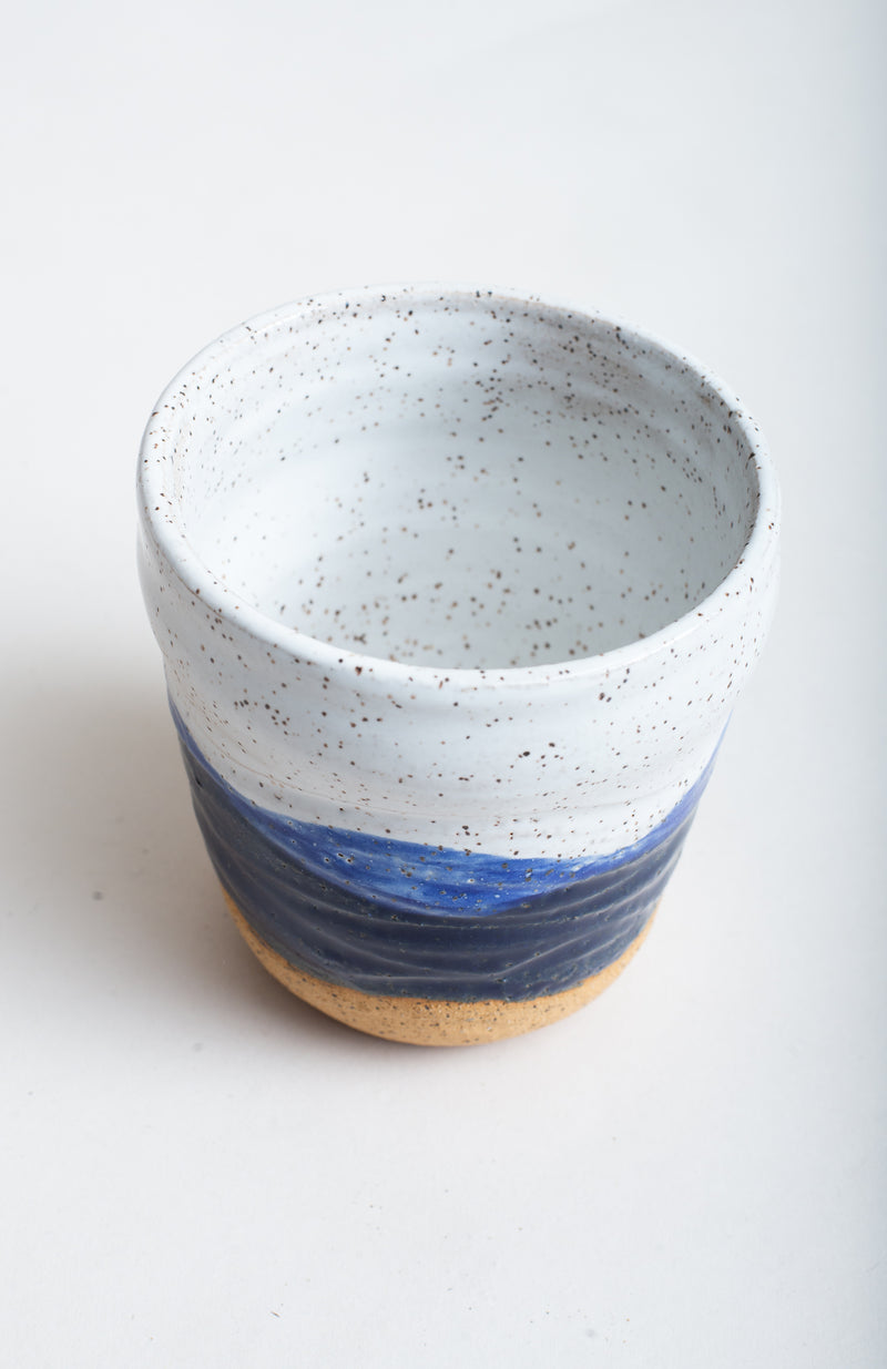 Hot or cold beverages can be served in this handmade ceramic mug.