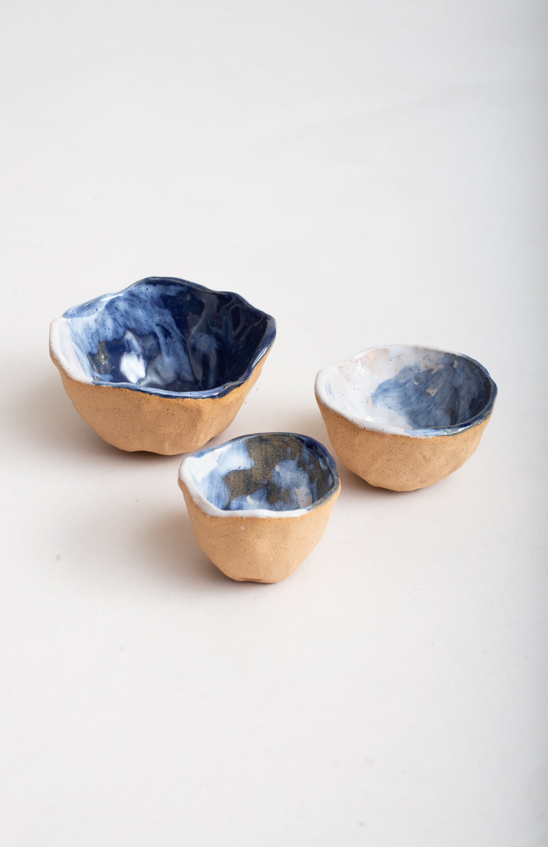 Raw ceramic is on the exterior of these bowls, a glazed surface is on the interior.