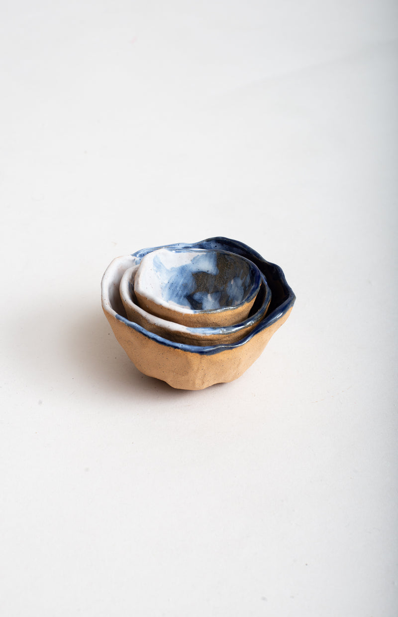 The handmade ceramic pinch bowls are designed to nest.