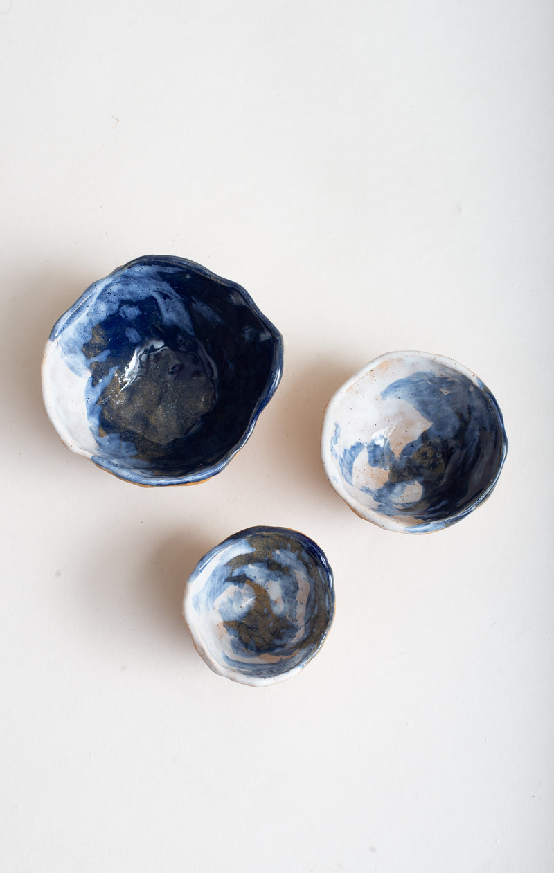 The blue storm motif is hand-painted on these handmade ceramic pinch bowls.