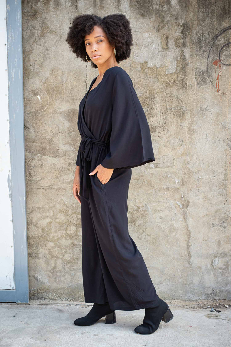A side view of the fair fashion Vanna jumpsuit that shows the wide sleeves and the pocket.