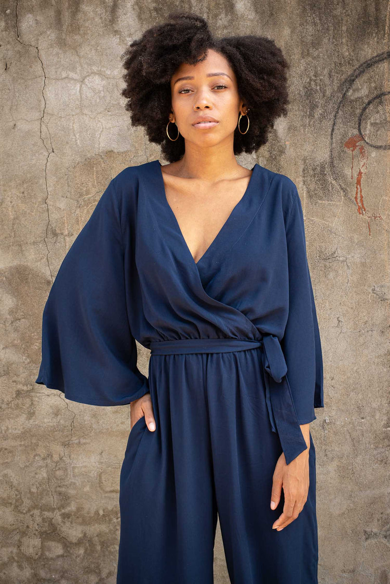 Our Vanna jumpsuit, seen here in navy, has a wrap top. Sustainably made in our fair fashion workshop.