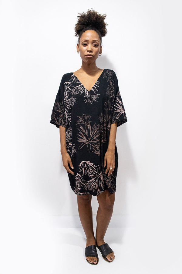 A front view of our ethically made Veha dress in black with a cactus print.
