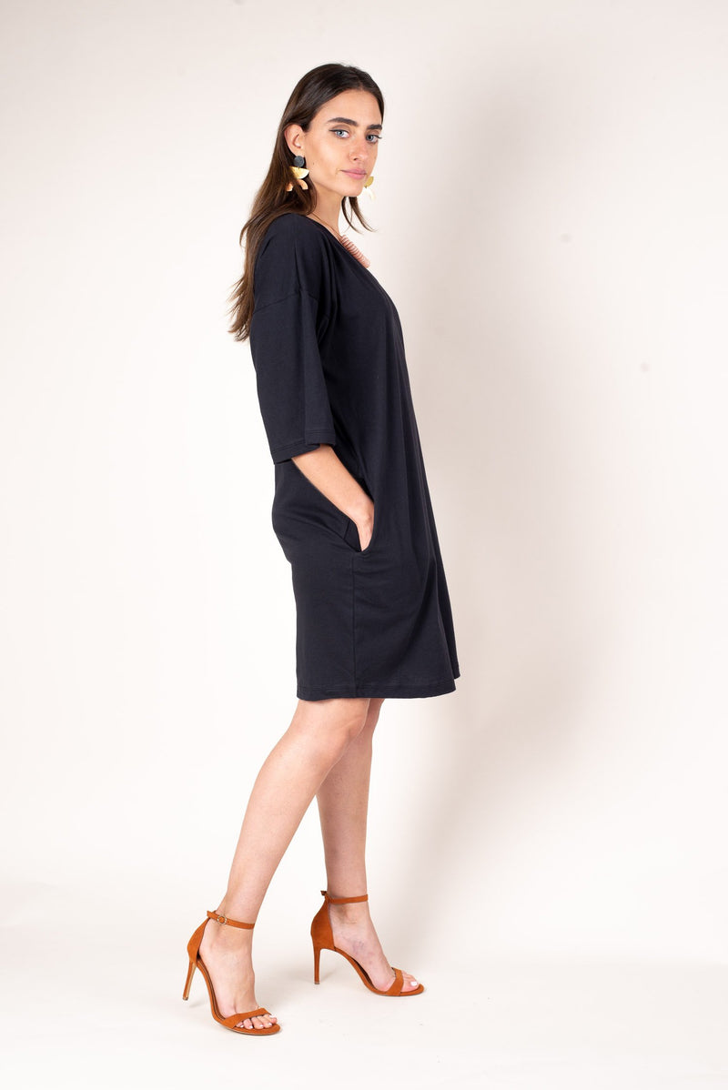A side view of the airy fit of the black veha t-shirt style dress with deep side pockets to easily stash essentials.