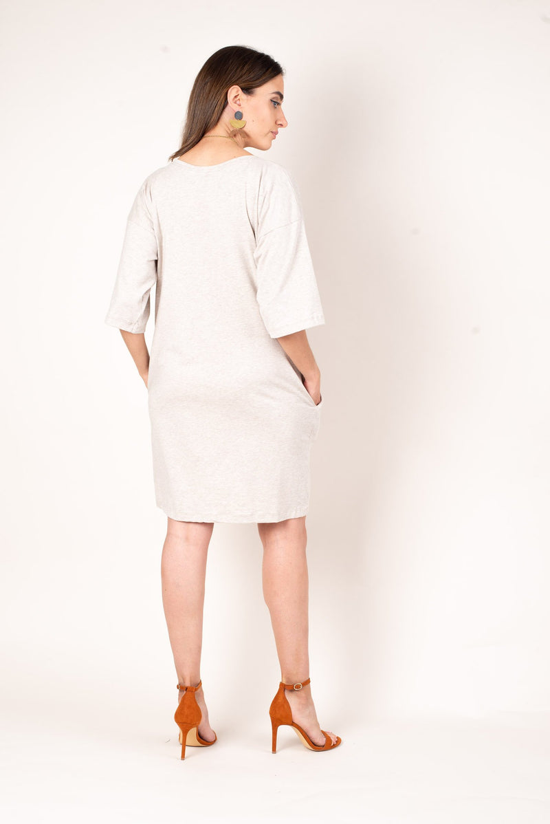The back of the oatmeal colored boxy t-shirt dress with a loose fit and elbow length sleeves.