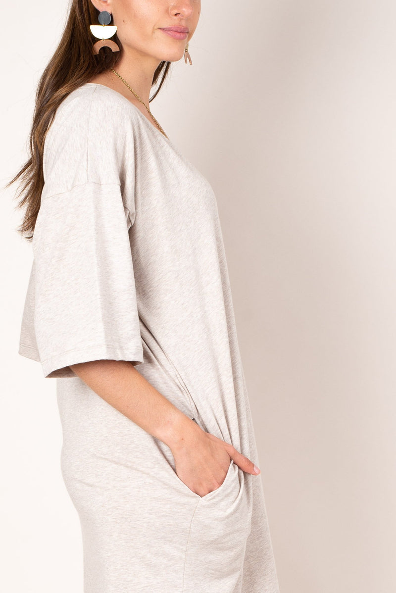 A close up view of the ultra soft and lightweight oatmeal colored reclaimed jersey of our v-neck t-shirt dress with deep side pockets.