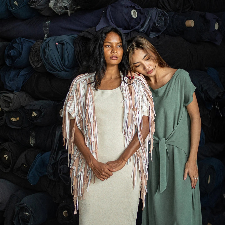 2 women wearing tonlé clothing in front of piles of deadstock textile waste