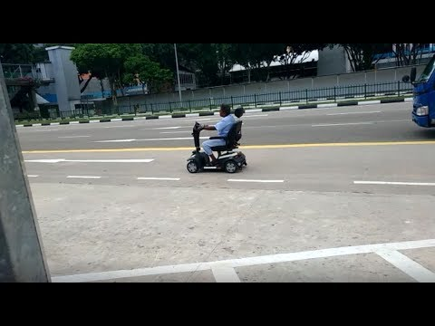 Man in Hospital Gown driving Mobility Scooter on Road